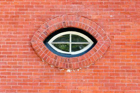 Cat eye shaped window in a red brick wall