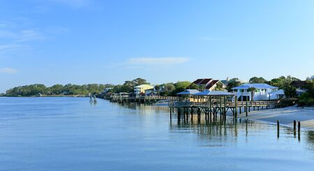 Early morning at the south end of Tybee Island beach. A view of a raised wooden docks and homes along Tybee Creek Stock Photo