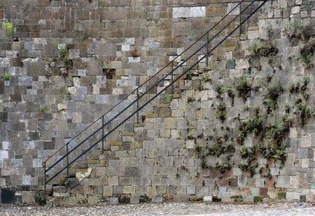 Stairs and iron railing along a stone wall near River Street in Savannah, Georgia