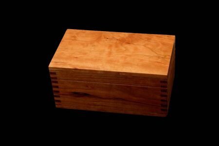 Cherry wood box with finger joints isolated on a black background.