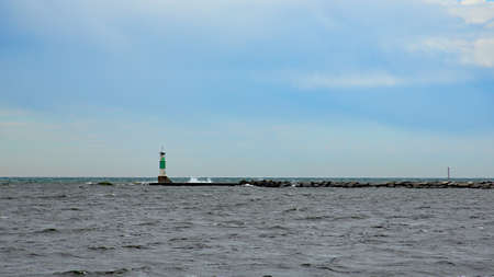 White and green lighthouse on Lake Michigan on a windy day at Muskegon