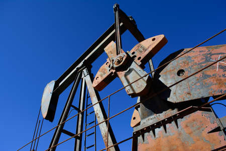 Rusty Oilfield Pumpjack (rocking horse) over a wellhead. Clear blue sky. Editorial