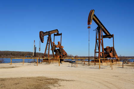 Two Rusty Oilfield Pump jacks (rocking horse) over a wellhead. Clear blue sky and lake background