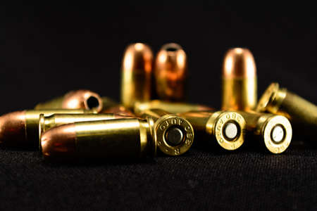 9mm ammo: 380 Auto bullets on black counter, black background, selective focus foreground