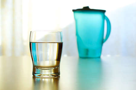 Cool and colorful glass of refreshing water with a full pitcher in the background Standard-Bild