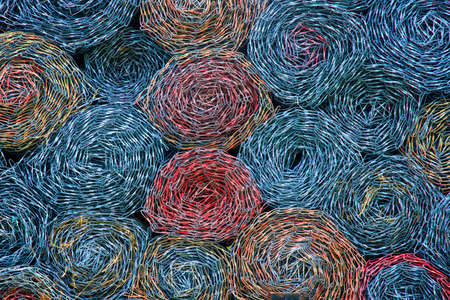Colorful rolled chain link, swirled and stacked in circle pattern.