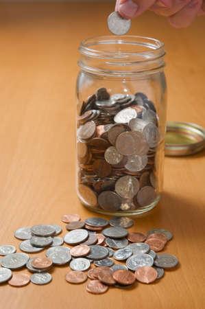 jarra: Monedas puestas en vasija, contando el cambio de repuesto en el escritorio