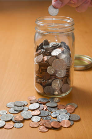 money jar: Putting coins in jar, counting spare change on the desktop