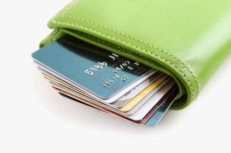 Groene leer portefeuille gevuld met krediet kaarten. Uitvoering van teveel krediet.