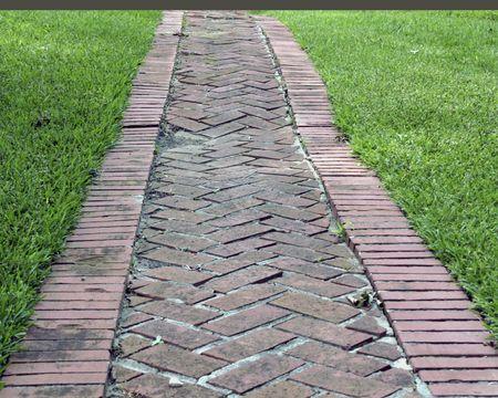 Red brick pathway through a park