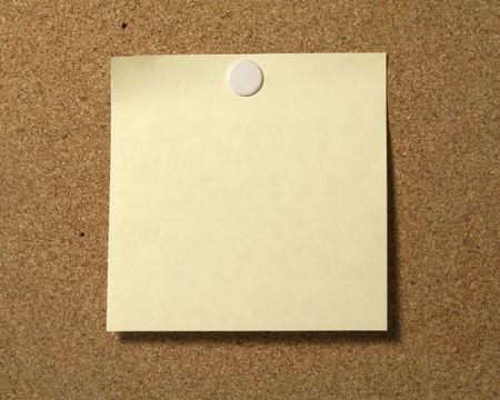 Blank post-it style note on corkboard.