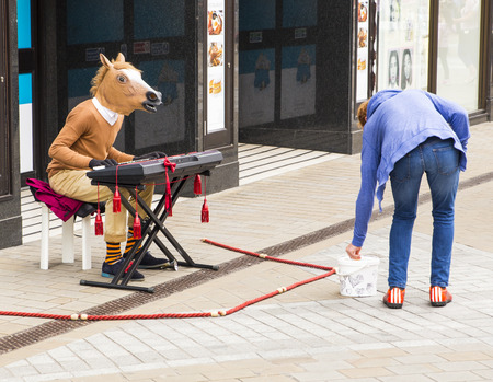 horse laugh: Man busking in city centre wearing a horses head