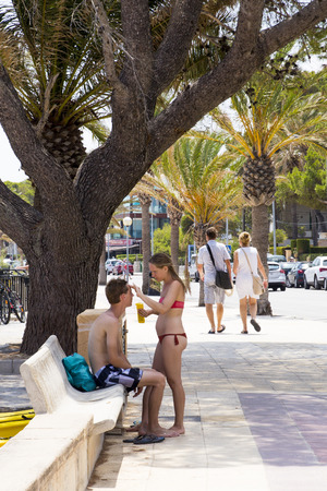 suncream: Photograph of a young couple putting sun cream on each other
