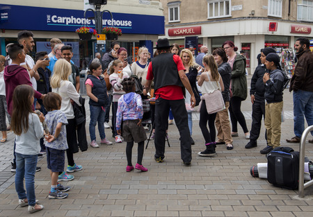 behind the scenes: Crowds watching a street performer busking