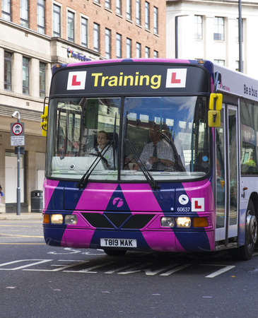 l first: Bus Driver.  Learner bus driver learning to drive a bus. Editorial