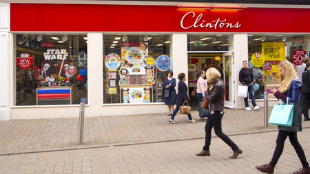 shop sign: People walking in front of the Clinton Cards shop during a busy shopping day in the centre of Leeds. Clintons is one of the largest card retailers in the UK highstreet