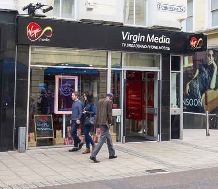 fixed line: LEEDS, UK - 5 SEPTEMBER 2015.  Virgin Media Shop in Leeds.  People walking in front of the Virgin Media shop in Leeds.  Virgin Media sells cable tv, fixed line telephone, broadband and mobile telephone services throughout England
