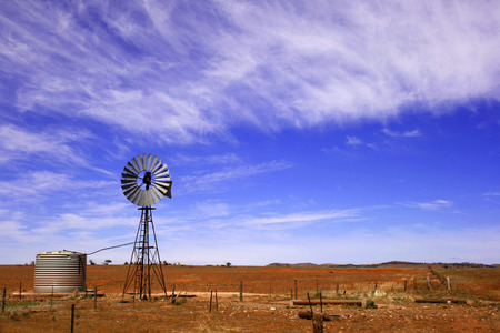 scrub grass: A wind driven waterpump in the desert landscape of South Australia