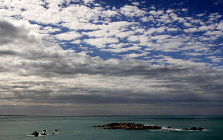 rainclouds: Rainclouds collect over a rocky coastline in South Australia Stock Photo