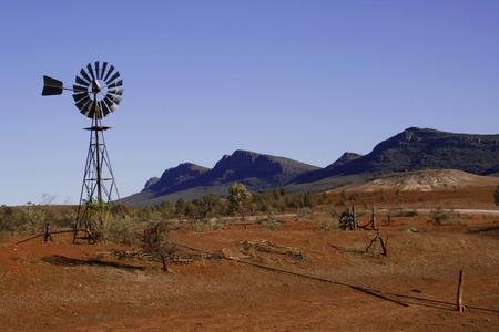 scrub grass: A wind driven waterpump in the desert landscape of the Flinders Ranges, South Australia