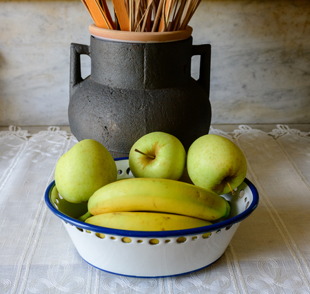 fruit still life with apple and bananas with dried flowers and jarron