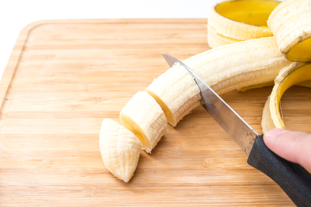 Male hands Cutting Banana on the kitchen board. Close-up. Selective Focus.