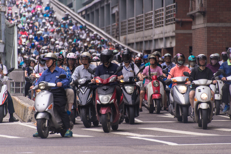 Taipei, Taiwan - July 6, 2018: Motorcycles go down the Taipei bridge during rush hour in the morning. Editorial