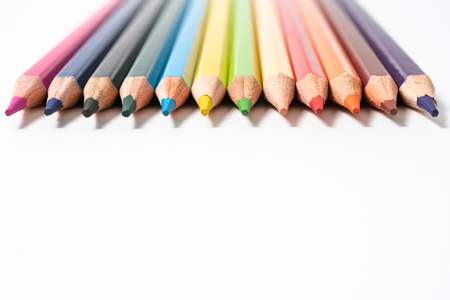 many colored pencils on white background