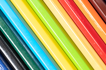 Colored pencils in a row isolated on white background.