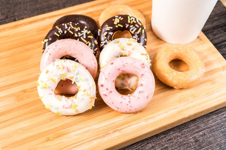 Donuts and coffee on wooden table. 版權商用圖片