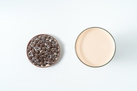 A glass cup of pearl milk tea (also called bubble tea) and a plate of tapioca ball on white background. Pearl milk tea is the most representative drink in Taiwan.