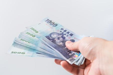 A hand holding a 1000 New Taiwan Dollar bill.