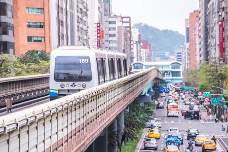 Taipei, Taiwan - April 13, 2019 : Taipei Metro Wenhu Line (Known as The Muzha Line Before Oct, 8, 2009). The Train Runs on Elevated Rails While Other Cars Jammed on The Roads.