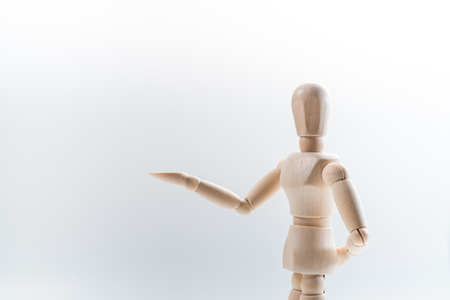 Wooden dummy proudly presents some invisible thing, isolated on white background, copy space for your object or text