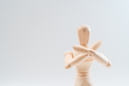 Refusal gesture, Wooden dummy, crossed hands on white background, copy space for your object or text Stockfoto