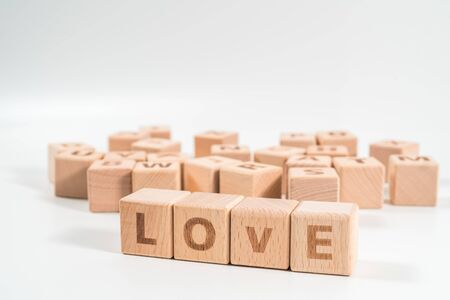 word LOVE on wood cube dices on white background.