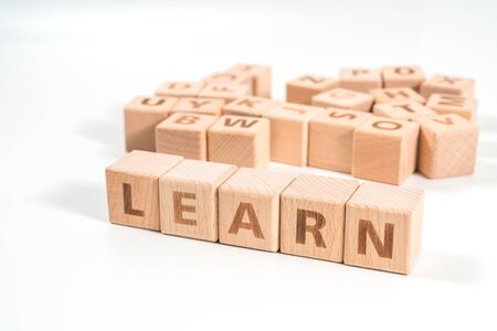 word LEARN on wood cube dices on white background.