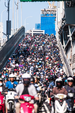 Taipei, Taiwan - September 25, 2019: Motorcycles go down the Taipei bridge during rush hour in the morning.