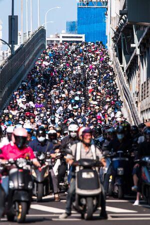 Taipei, Taiwan - September 25, 2019: Motorcycles go down the Taipei bridge during rush hour in the morning.