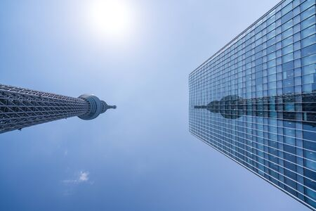 TOKYO, JAPAN - March 27, 2019: A part of Japan Tokyo skytree tower building with blue sky, Reflection of Tokyo SkyTree on another building.