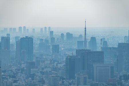 Staub tagsüber in einer stark verschmutzten Stadt - in diesem Fall Tokio, Japan. Stadtbild von Gebäuden mit schlechtem Wetter aus Feinstaub. Luftverschmutzung.