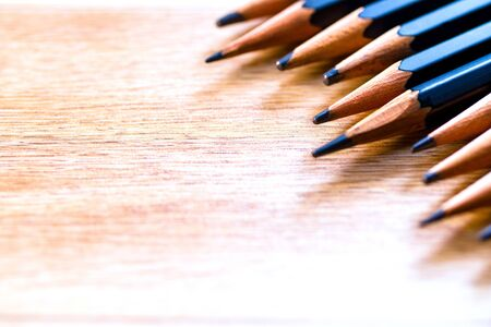 black pencils isolated on wood surface background.Close up.