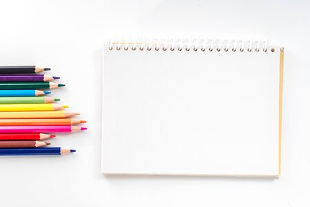 notepad with color pencil on white table view from above