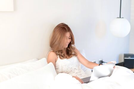 Young beautiful Asian female using laptop or notebook for working at home or shopping online while laying on bed in her bedroom. Communication Technology, marketing online, social media concept.