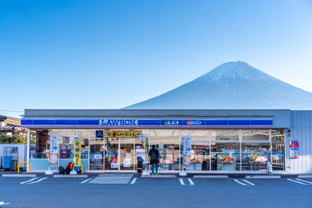 YAMANASHI, JAPAN - November 19, 2019: View of Lawson shop with mountain Fuji behind at Kawaguchiko station. Lawson is convenience store with branches all over Japan. Editorial