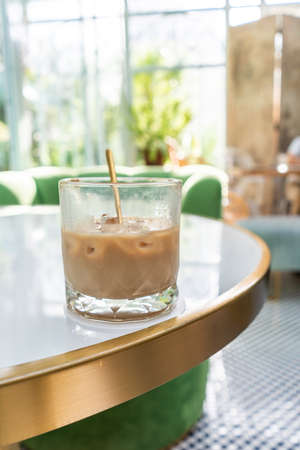 Ice coffee in a tall glass with milk poured over Foto de archivo