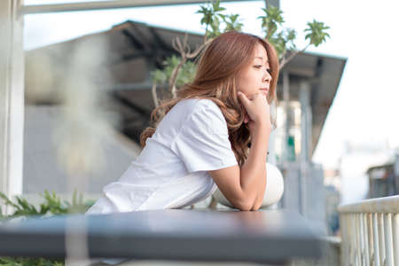 Young woman enjoying the cityscape side view from her hotel.