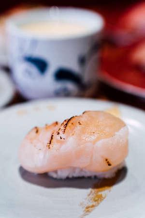 Sushi and Sashimi. Dishes of Sushi and Sashimi rolling on conveyer belt. Stock Photo