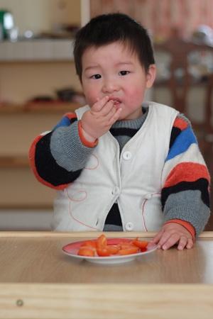 gar�on chinois mangent des fruits Banque d'images