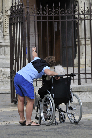 disabled in his wheelchair accompanied by a volunteer